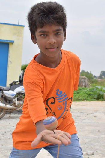 Portrait of boy playing spinning top