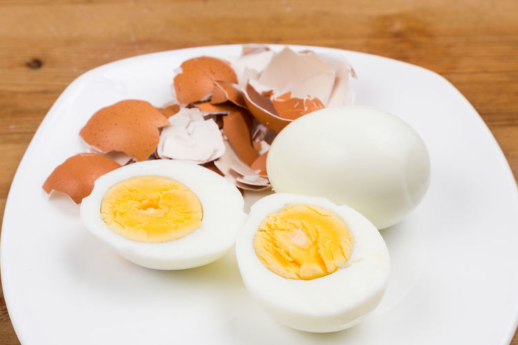 Peeled egg cut into half on plate with shell. Nutritious breakfast. Boiled Boiled Egg Breakfast Close-up Egg Egg Yolk Food Food And Drink Freshness Healthy Eating High Angle View Indoors  Meal No People Plate Ready-to-eat Serving Size Still Life Table Wellbeing