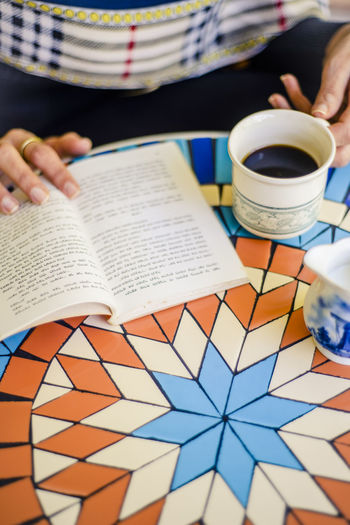 Midsection of person holding coffee cup on table