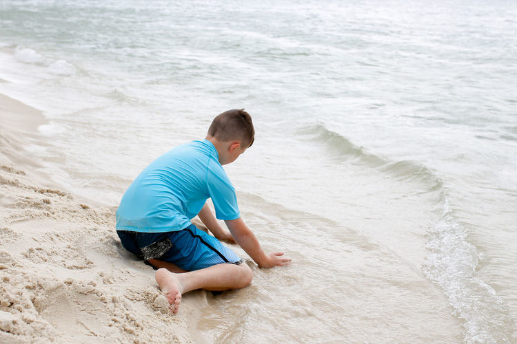 Boy Playing in the Sand on the Beach Beside the Shore of Destin Beach One Person Sand Water Leisure Activity Vacations Boy Childhood Childhood Memories Sky Vacations Summer Vacation Summertime Beach Fun Beach Photography Relaxation Trip Family Vacation Vacation Destination