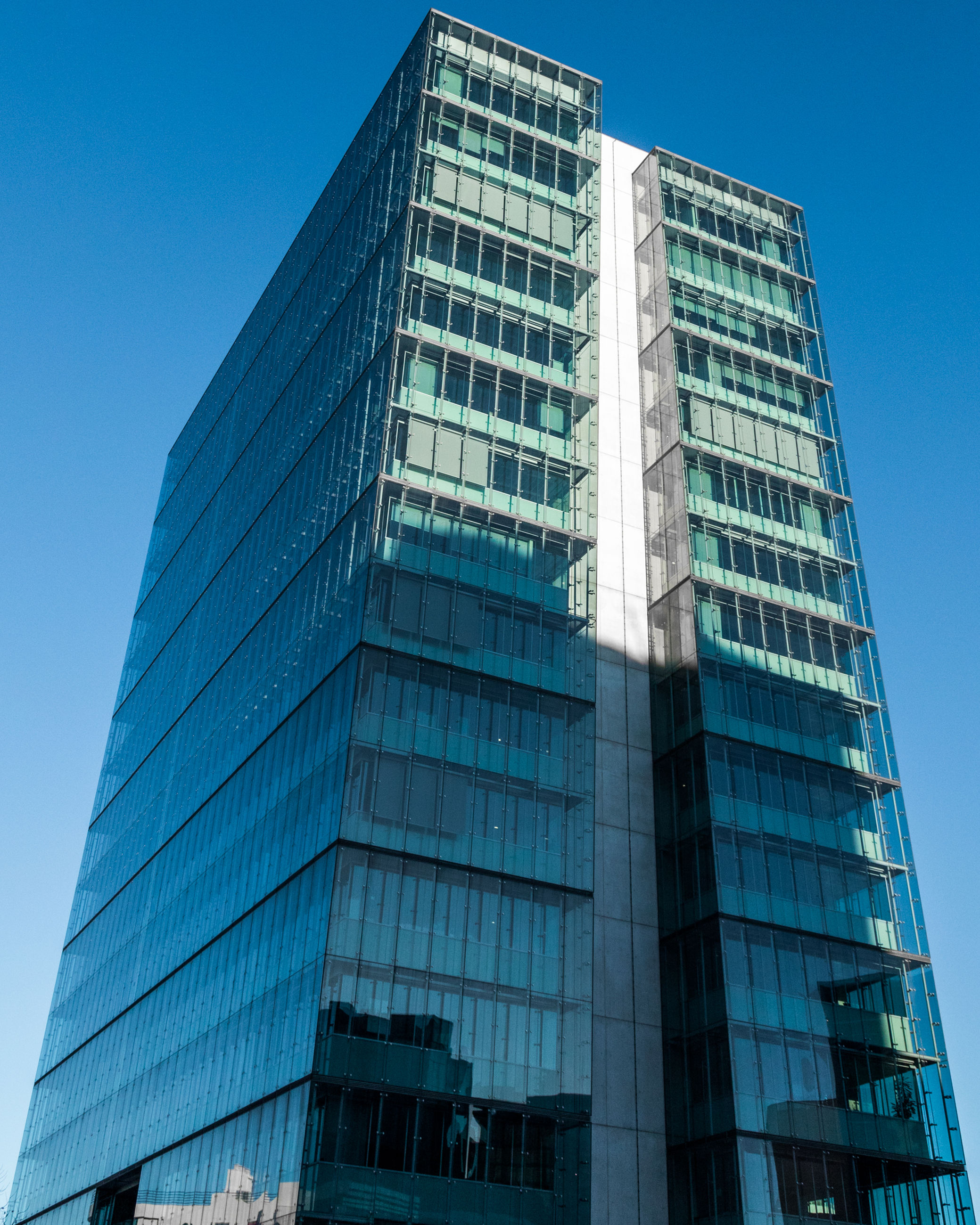 built structure, low angle view, architecture, building exterior, office building exterior, modern, sky, office, city, clear sky, glass - material, building, no people, blue, tall - high, skyscraper, nature, reflection, day, tower