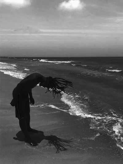 Side view of man tossing hair at beach against sky