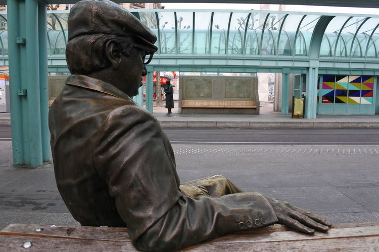 Adult Bench Day Mammal Man Men One Person Outdoors People Real People Rear View Social Issues Statue Tram Stop