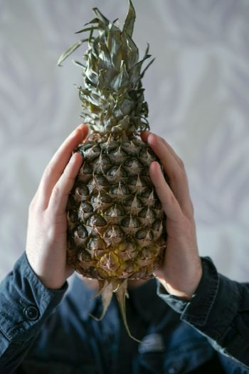 Close-Up Of Hand Holding Pineapple