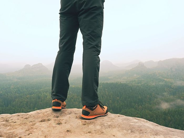 Male legs in dark hiking trousers and leather trekking shoes on peak of rock above misty valley