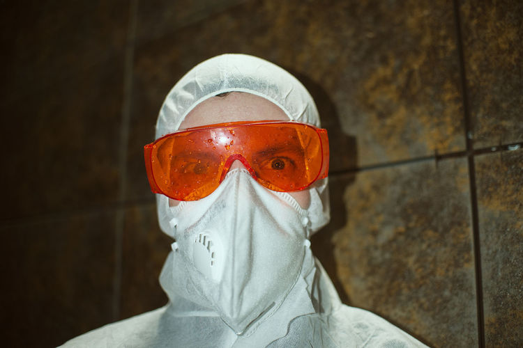Portrait of person wearing mask against wall