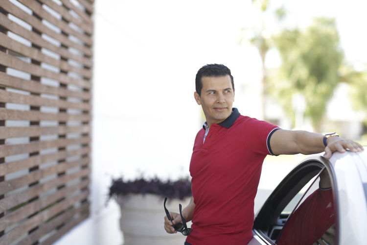 Smiling man standing by car in city