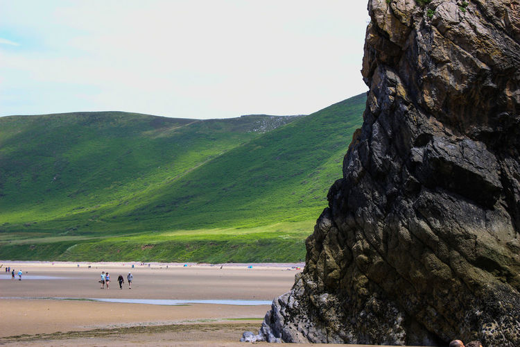Rock formation at beach against sky