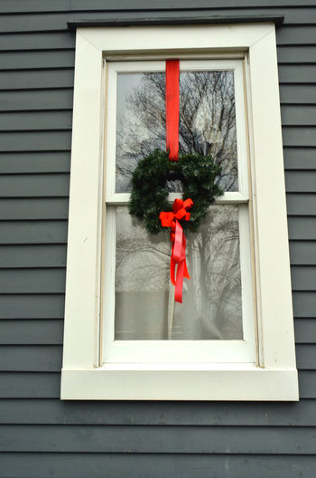 window with holiday wreath and rd ribbon Architecture Building Exterior Built Structure Christmas Decorations Day Holiday Decorations House No People Outdoors Red Red Ribbon Bow Window Window Sill Wreath