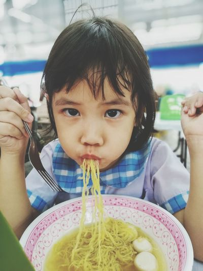 Portrait Of Cute Girl Eating Noodle Soup In Restaurant