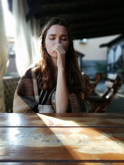 Thoughtful woman with closed eyes wrapped in blanket sitting at restaurant