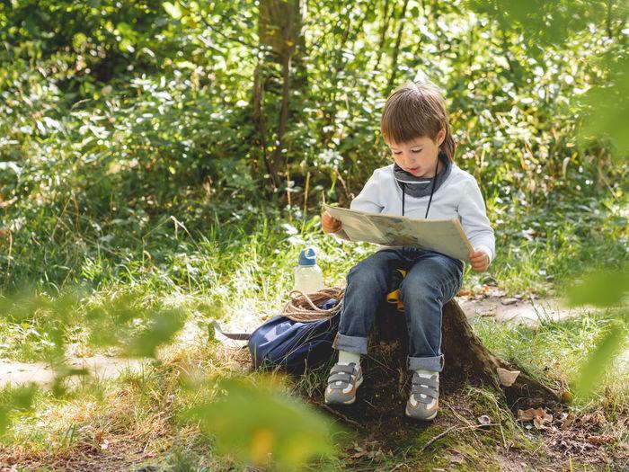 Full length of boy sitting on land