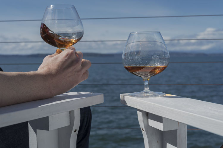 Cropped hand of man holding brandy snifter on white adirondack chairs against sea