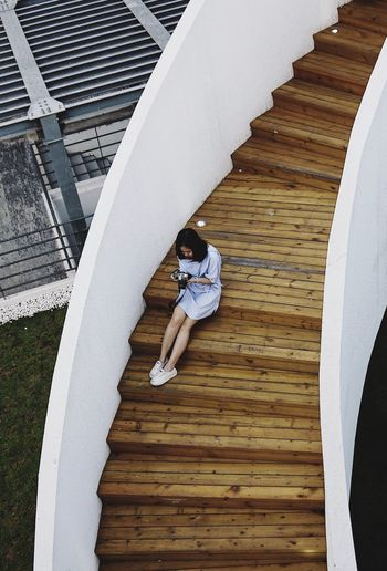 High Angle View Full Length Architecture Staircase One Person Real People Leisure Activity Lifestyles Steps And Staircases Built Structure Casual Clothing Pattern Outdoors Young Adult Relaxation
