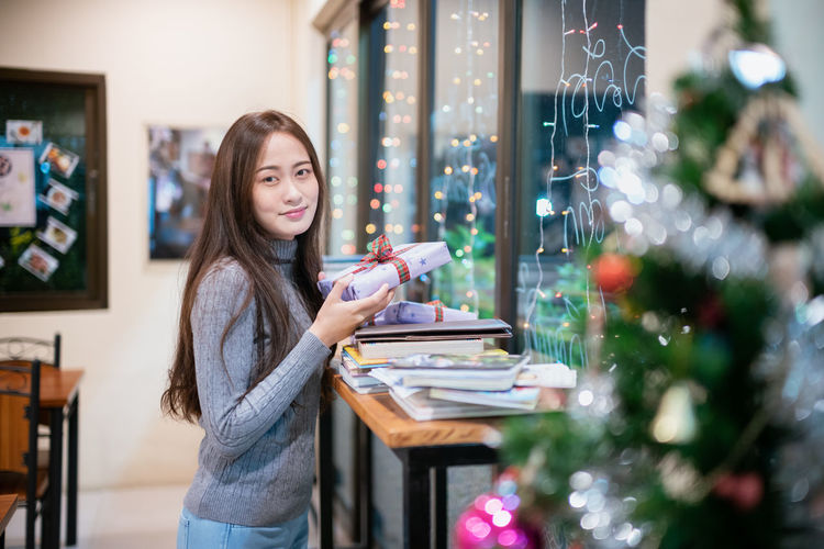 Side view of young woman holding christmas present while standing at home
