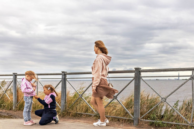 Rear view of women standing on railing against cloudy sky