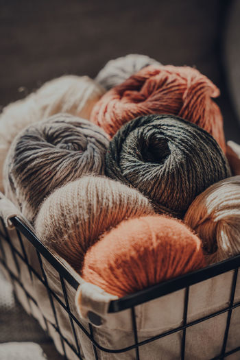 Close up of balls of earth coloured yarn inside a basket, sunlight from the window on it.