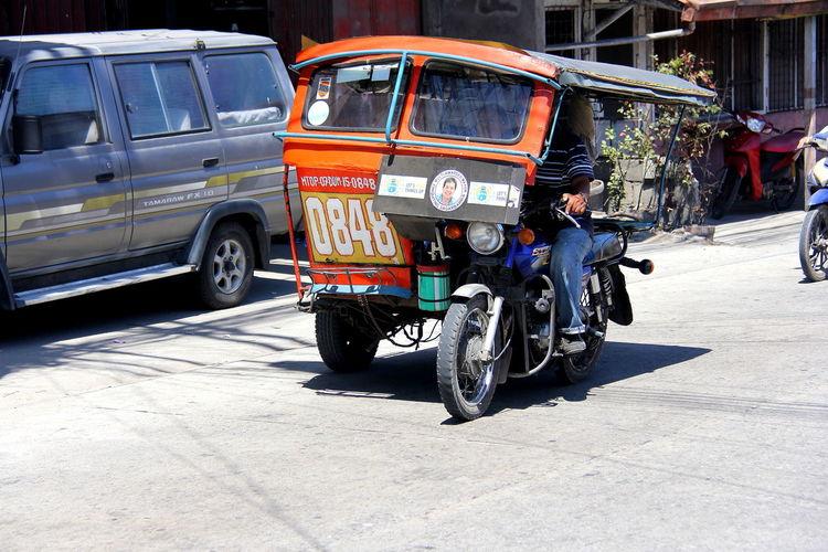 Man driving jinrikisha on city street