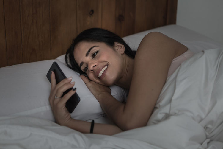 Young woman using phone while lying on bed at home