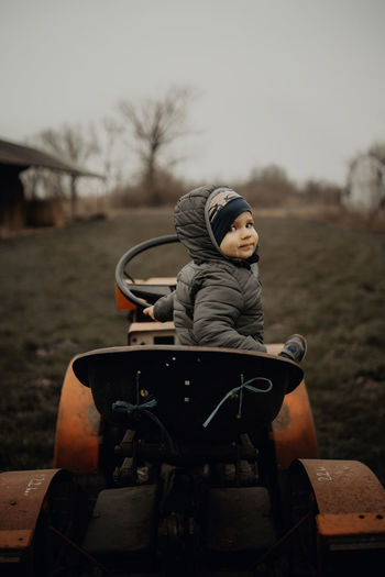 Portrait of cute boy sitting on toy car