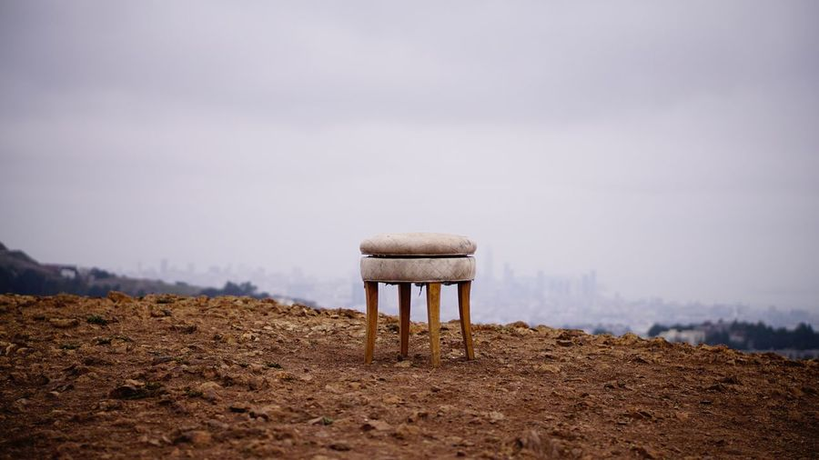 Stool on field against sky