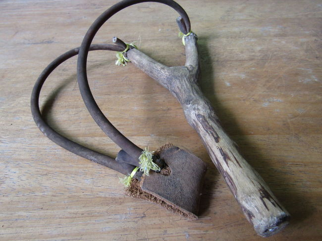 Old wooden slingshot on the wooden table Leather Retro Security Sling Target Wood Aim Childhood Closeup Elastic Game Gun Sling Hunt Object Old Play Safety Shot Simple Slingshot Table Toy Vintage Weapon Wooden