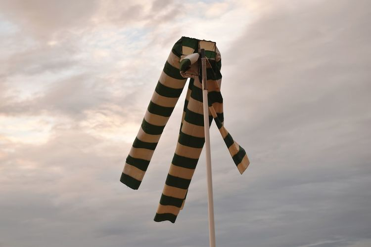 Low angle view of windsock on pole against cloudy sky