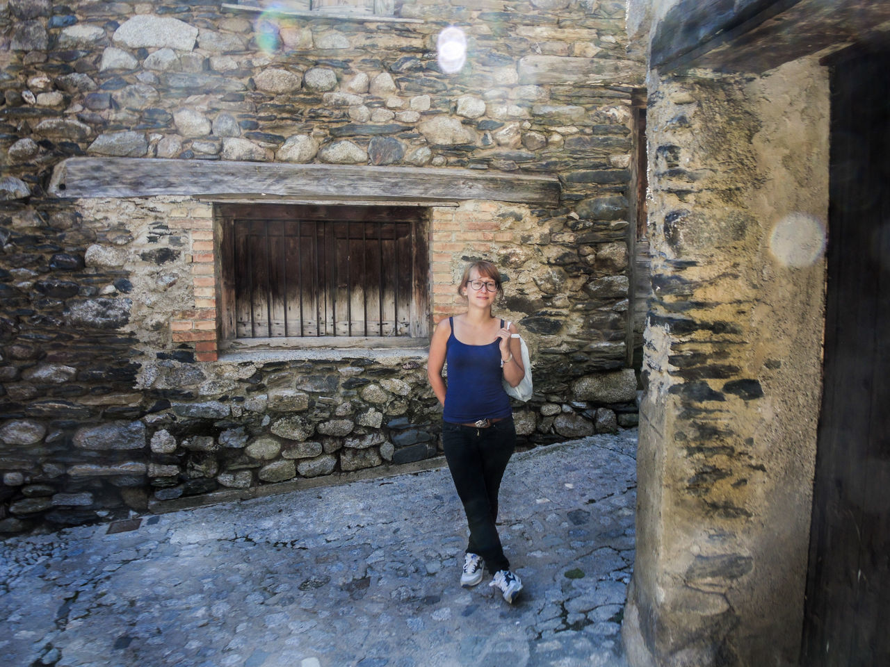 one person, full length, adult, women, architecture, front view, day, standing, young adult, portrait, lifestyles, history, looking at camera, wall, built structure, smiling, real people, stone wall, fashion, outdoors, hairstyle