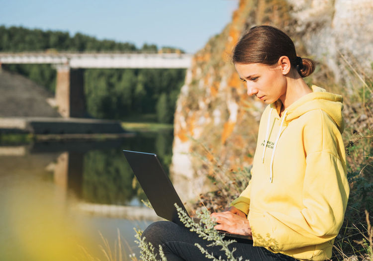 Young woman traveler freelancer in yellow hoodie with opened laptop on background