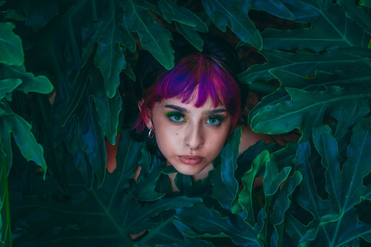 Portrait of young woman amidst plants