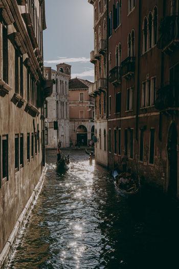 Gondolas on a narrow canal in venice, italy.