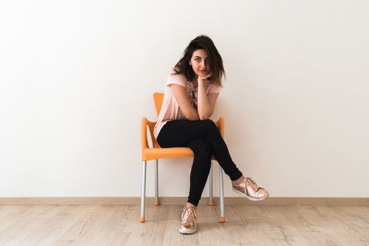 Portrait of young woman sitting on hardwood floor against white background