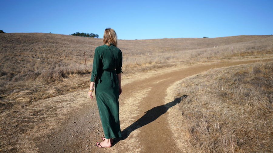 Rear view of woman standing on dirt road against sky