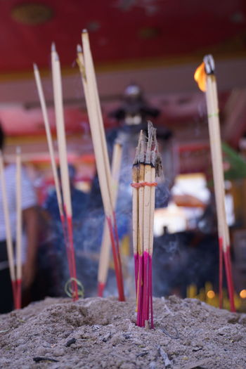 Close-up of incenses burning at temple