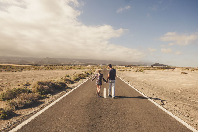 Young couple walk together on a long straight road in the middle of a desert nowhere place - life and love and relationship concept with youth people walking hand to hand - summer time Full Length Rear View Sky Real People Lifestyles Women Togetherness Men Adult Cloud - Sky Nature Road Leisure Activity People Two People Direction Landscape Beauty In Nature Scenics - Nature Non-urban Scene Couple - Relationship Outdoors Positive Emotion Arid Climate Caucasian Mountains