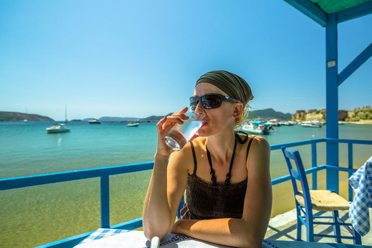Woman drinking water while sitting at restaurant over sea against clear blue sky