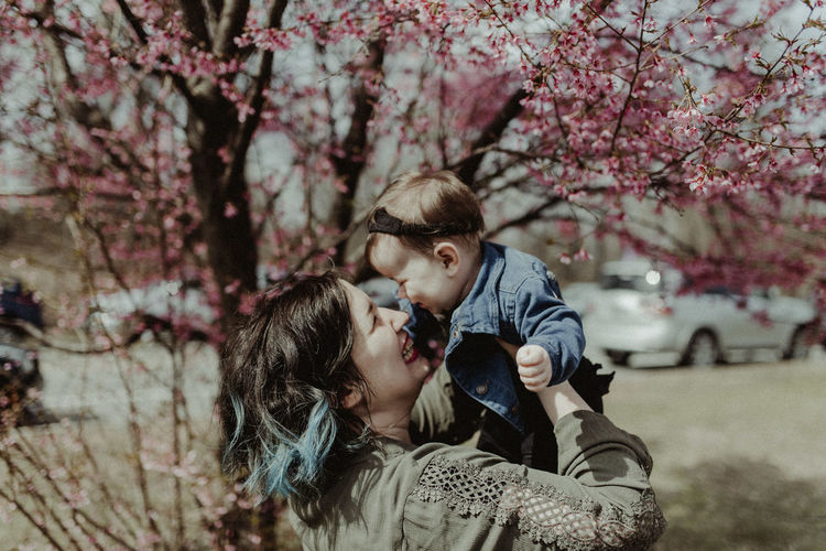 Mother and daughter against tree