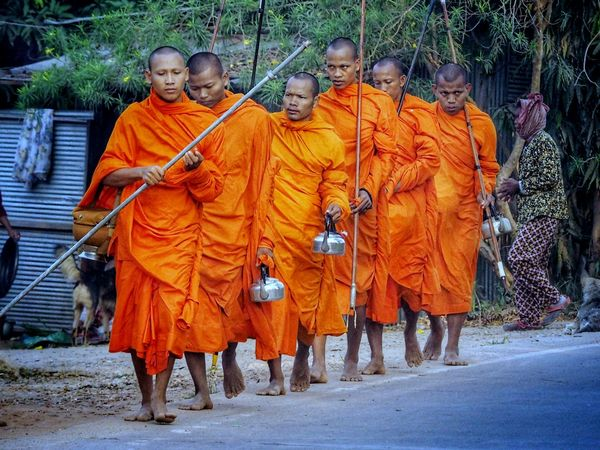 Six Cambodian monks, carrying long spears and kettles, walk along the side of the road, collecting alms, on a special Buddhist day called, Boreva. Monks Cambodian Monks Tradition History Orange Robes Buddhism Buddhist Road Spear Kettle Religion Religion And Tradition Color Orange Orange Color Religion Adult Full Length Tradition