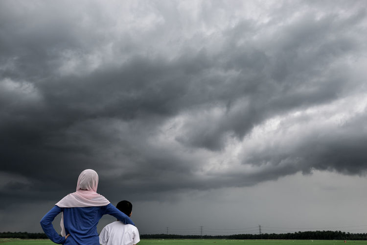 Rear View Of Mother And Son Standing On Field Against Cloudy Sky