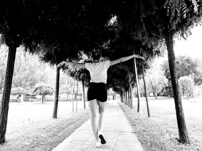 EyeEmNewHere Walking Around Adult Arms Spread Beauty In Nature Day Full Length Happiness Leisure Activity Lifestyles Nature One Person Outdoors Park - Man Made Space People Real People Rear View Road Sky Tree Tree Trunk Women Young Adult Young Women
