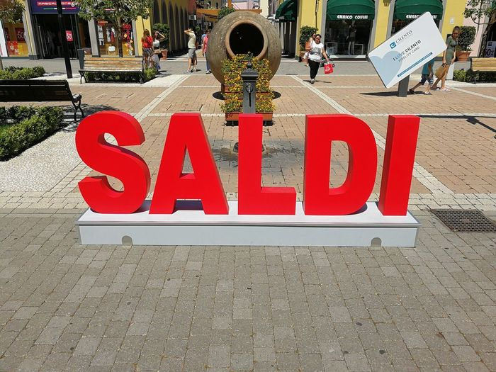 Saldi al centro commerciale di Battipaglia Battipaglia Architecture Building Exterior Built Structure Capital Letter Centro Commerciale City Communication Day Footpath Guidance Incidental People Information Information Sign Nature Outdoors Paving Stone Red Saldi Sign Street Symbol Text Western Script
