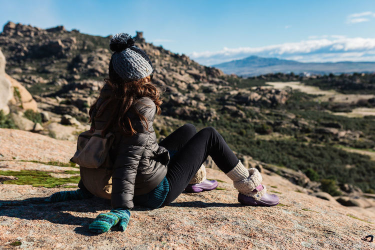 Midsection of woman sitting on rock against sky