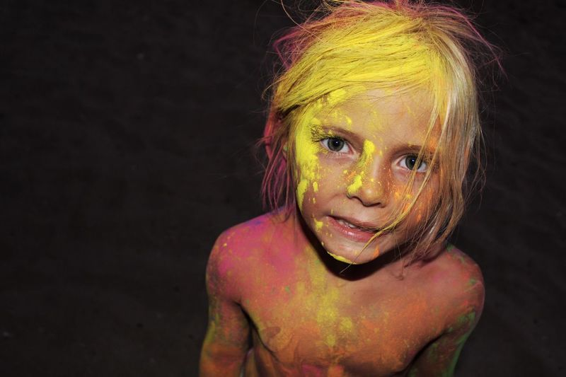 High angle portrait of shirtless girl covered with powder paint at night