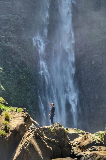 Man taking selfie against waterfall