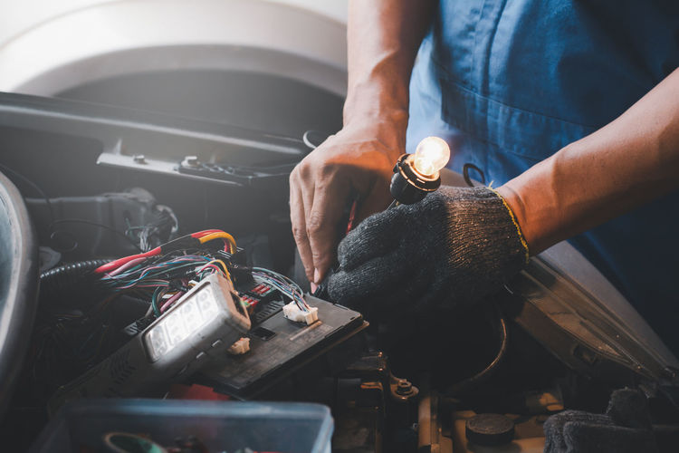 Midsection of repairman working at garage