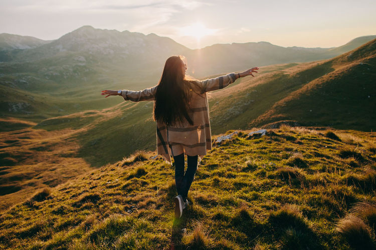 Rear view of woman with arms outstretched on mountain against sky during sunset