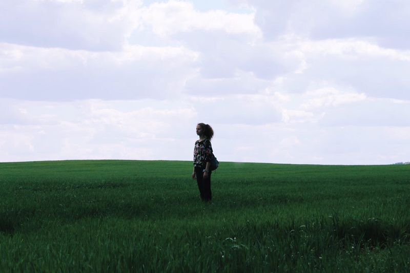 Woman Standing On Agricultural Field Against Sky
