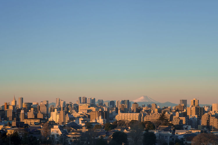 Tokyo CityScape with Sunset Twilight ASIA Japan Mt.Fuji Tokyo Twilight Architecture Building Exterior Built Structure City Cityscape Clear Sky Day Modern Mountain No People Outdoors Sky Skyscraper Sunlight Sunset Travel Destinations Urban Skyline Vintage