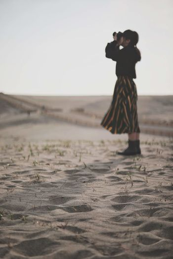 Woman standing on beach against clear sky