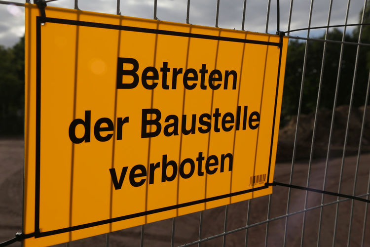 Close-up of yellow warning sign on metal gate